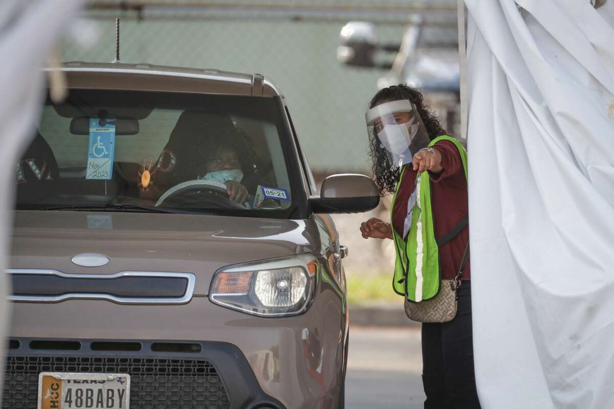 A Voter Assistant aids a drive-thru voter at the Houston Food Bank, which is operating an early voting site for the first time Tuesday, Oct. 13, 2020, in Houston.