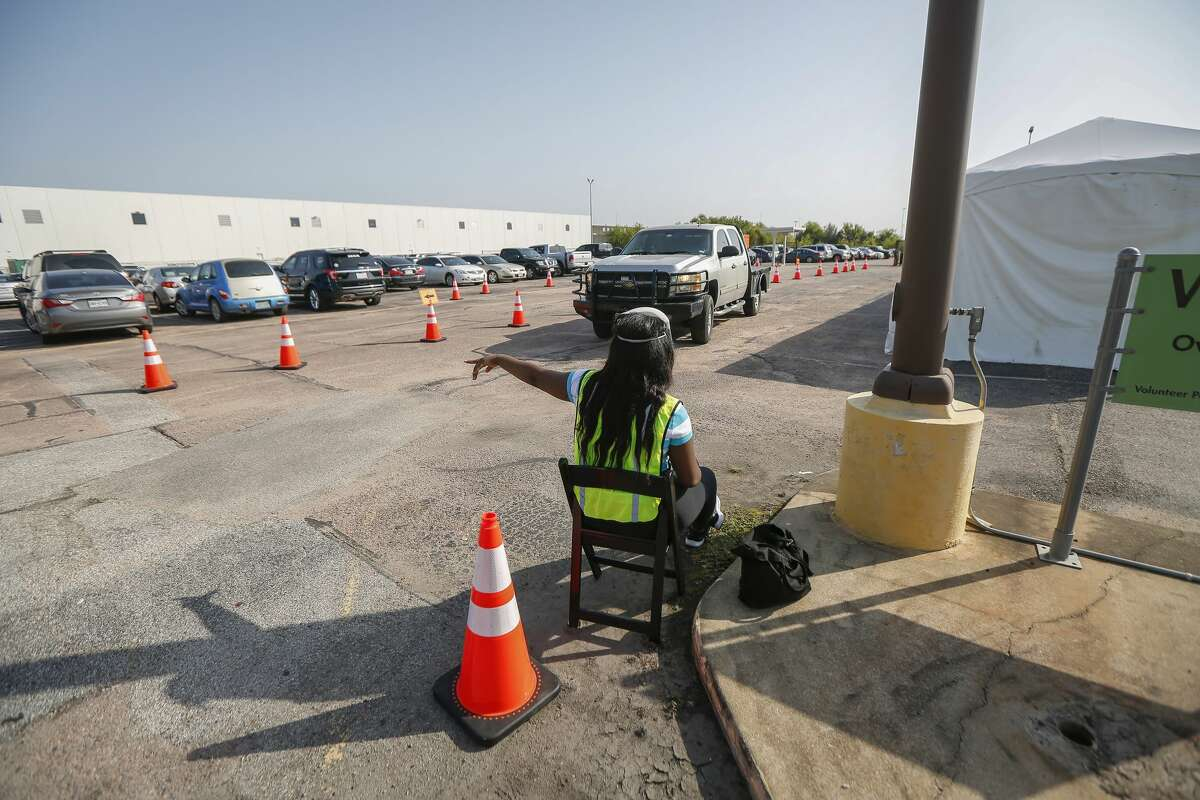 A Voter Assistant aids a drive-thru voter with exiting at the Houston Food Bank, which is operating an early voting site for the first time Tuesday, Oct. 13, 2020, in Houston.