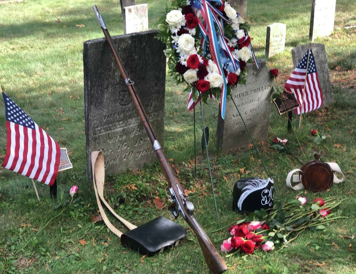The Roger Sherman Chapter, Daughters of the American Revolution held a grave marking dedication ceremony for the Revolutionary War services of two African-American soldiers from New Milford, Samuel Phillips and Jeruel Phillips Sunday at Center Cemetery in town. Above, a soldier's acoutrements - a helmet, a cartridge box, a musket and a canteen - are placed in front of their gravestones by Lt. Russ Kenney of the 6th Connecticut Regiment.