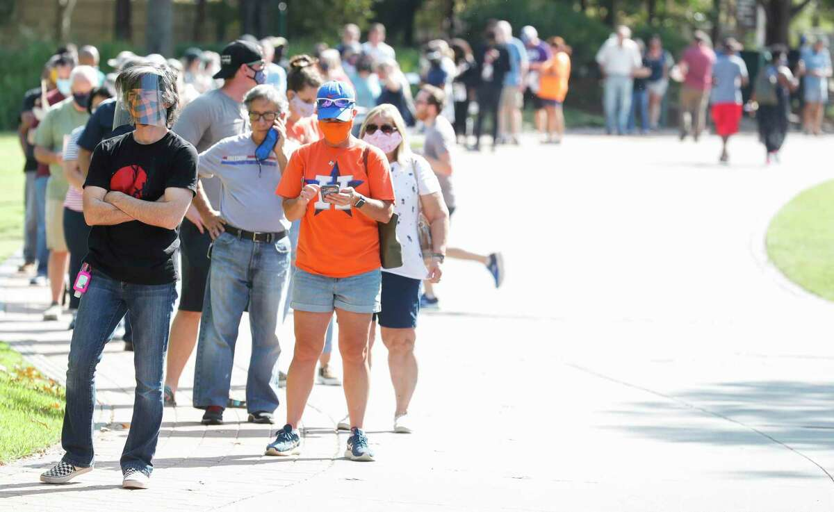 Residents wait in line along Town Green Park to vote at the South Montgomery County Community Center on the first day of Early Voting, Tuesday, Oct. 13, 2020, in The Woodlands.