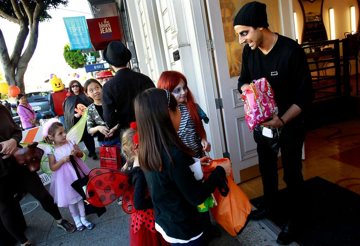 Rocky, at the MAC cosmetic store on Union Street, hands out candy to students from Sherman Elementary School in San Francisco.