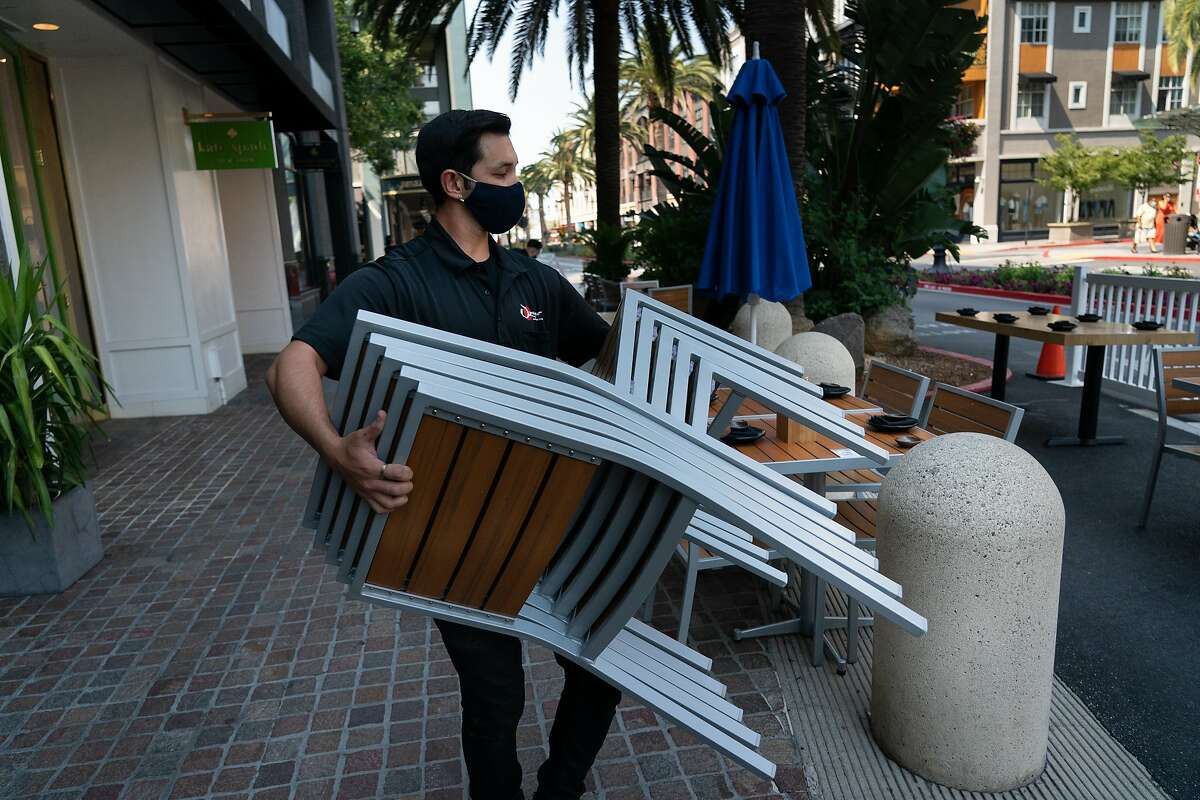 Marcus Hoang sets up outdoor seating for dinner at Ozuma along Santana Row in San Jose in July. Some health experts continue to warn against indoor dining, making outdoor
