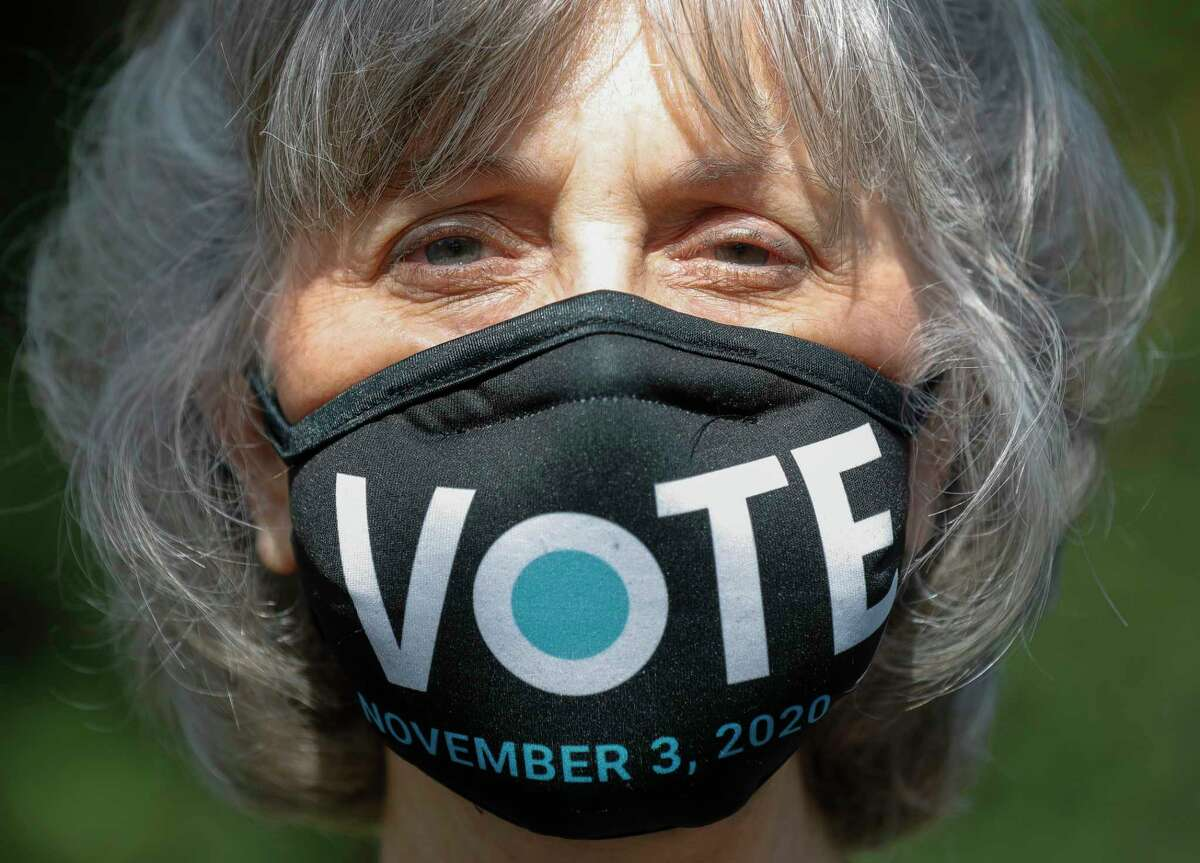 Penny Bradshaw wears a mask encouraging people to vote on the first day of Early Voting, Tuesday, Oct. 13, 2020, in The Woodlands.
