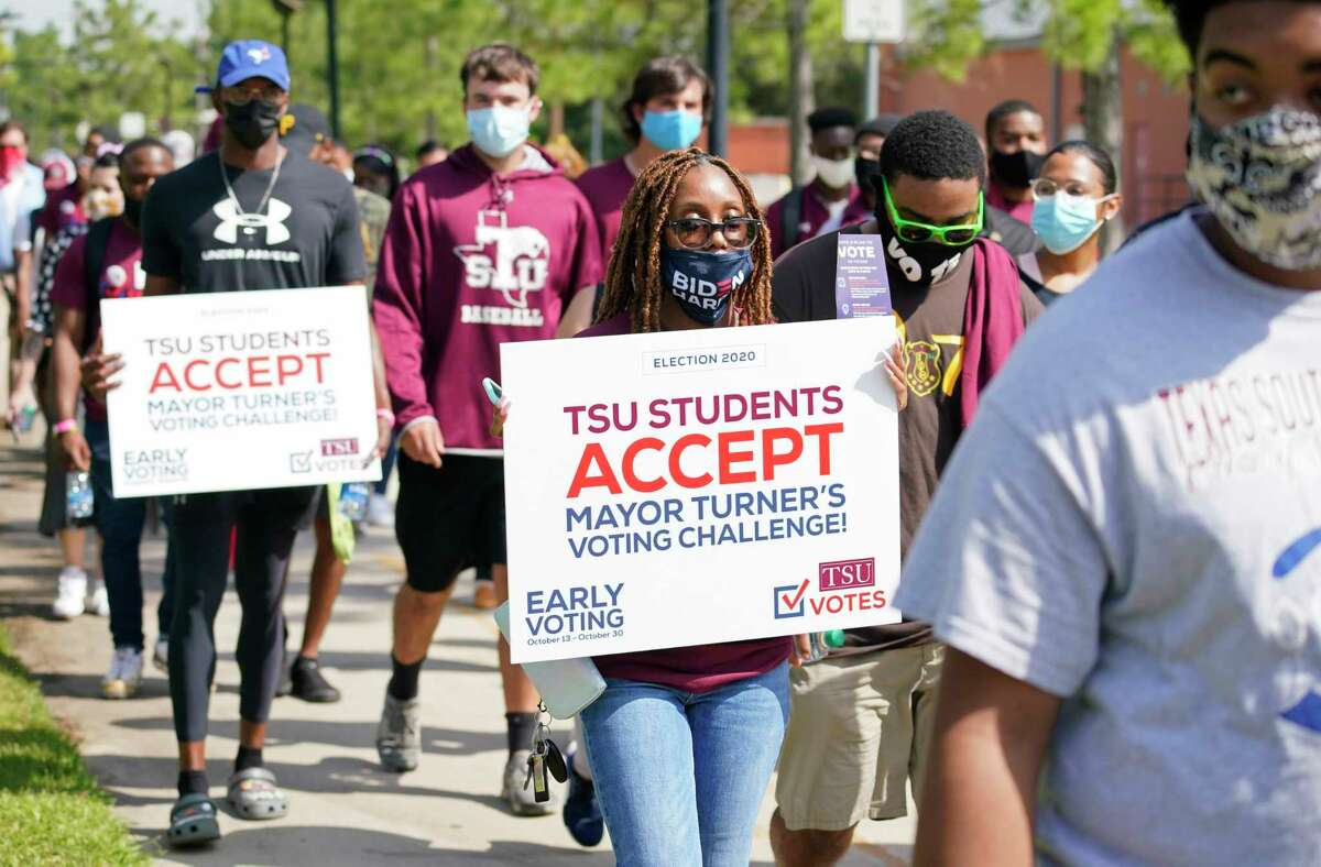 People walk during the march to the polls event to kick off early voting at Texas Southern University Tuesday, Oct. 13, 2020 in Houston. Mayor Sylvester Turner issued a voting challenge among TSU, Rice and the University of Houston.