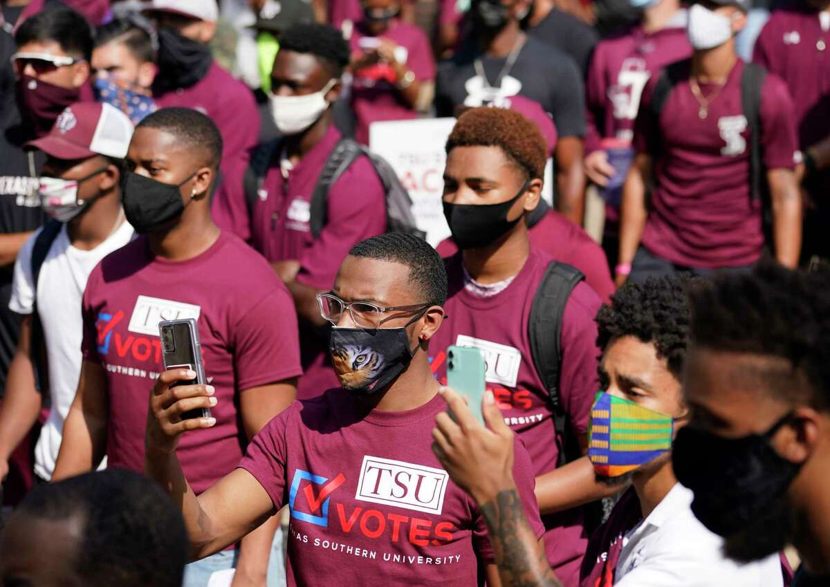 People listen to Mayor Sylvester Turner speak during the march to the polls event to kick off early voting at Texas Southern University Tuesday, Oct. 13, 2020 in Houston. The mayor has issued a voting challenge among TSU, Rice and the University of Houston.