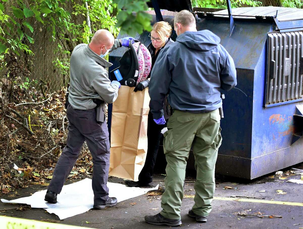 New Haven police investigate the scene where an 8-month-old girlwas found alive in a dumpster outside an apartment complex Monday at 575 Dixwell Ave. in New Haven. Here, a car seat is taken from the dumpster.