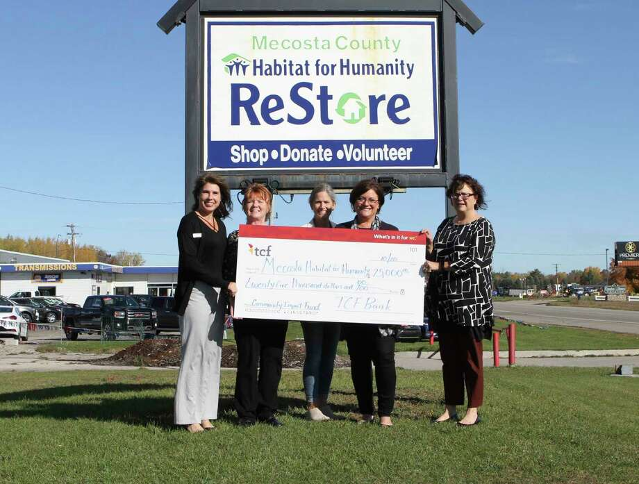 Representatives with TCF Bank presented Mecosta County Habitat for Humanity with a check for $25,000 Tuesday morning at the organization's ReStore. (Pioneer photo/Taylor Fussman)