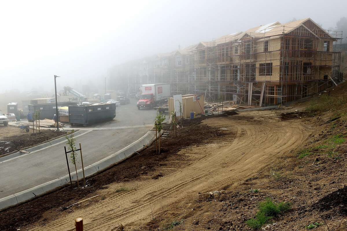 Fog shrouds new homes under construction last month in South San Francisco. Sales are expected to grow next year, after being dampened by pandemic restrictions this year.