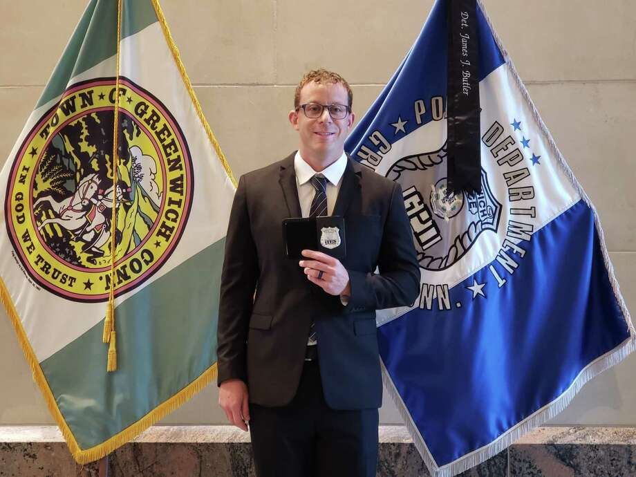 Officer Joshua Weinstock, the newest member of the Greenwich Police Department, displays the badge he was given at police headquaters. Photo: / GPD