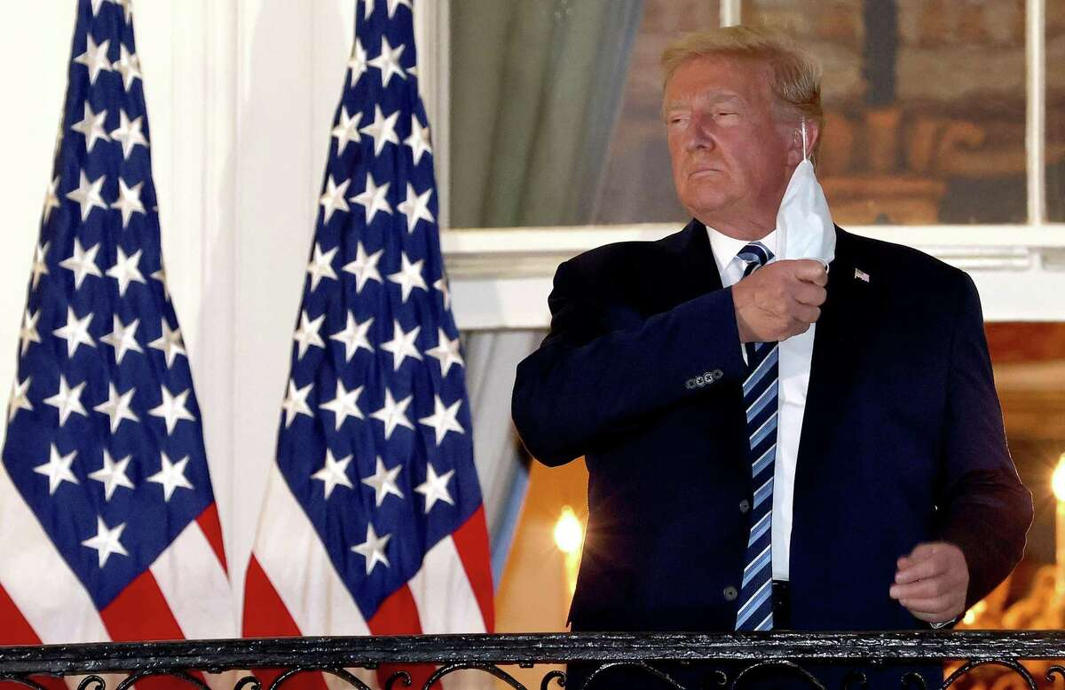 U.S. President Donald Trump removes his mask upon return to the White House from Walter Reed National Military Medical Center on Oct. 5. Just what message was he trying to send? Why are we still fighting over masks?