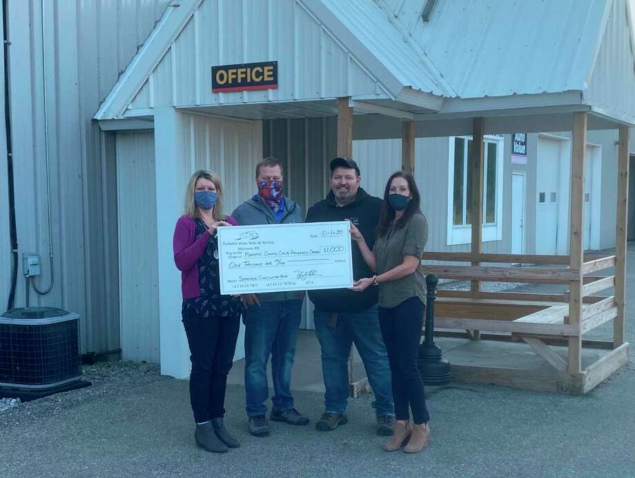 Tyler Reed and John Reed, co-owners of Parkdale Auto Sales and Service, present a check for $1,000 to Traci Smith and Megan McCarthy of the Manistee County Child Advocacy Center. The center was the company's September charity of the month. (Courtesy Photo)