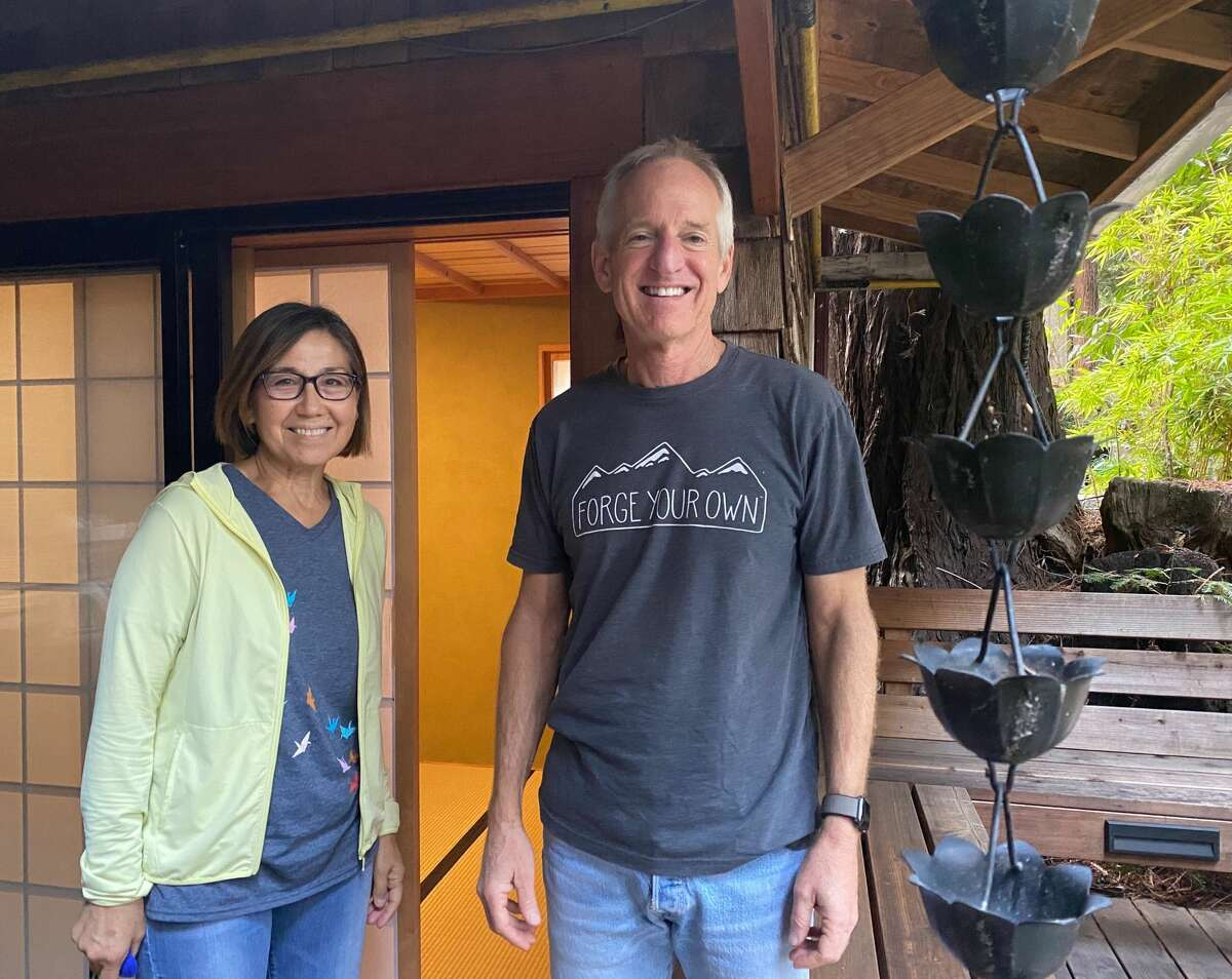 Ann and Peter Jordan stand in front of their Japanese-inspired Airbnb.