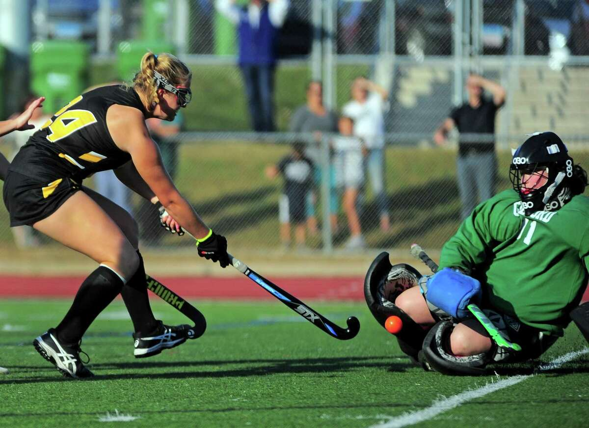 Gilford goalie Eve Young blocks a shot attempt by Daniel Hand's Grace Goddard, left, during field hockey action in Guilford, Conn., on Tuesday Oct. 1, 2019.