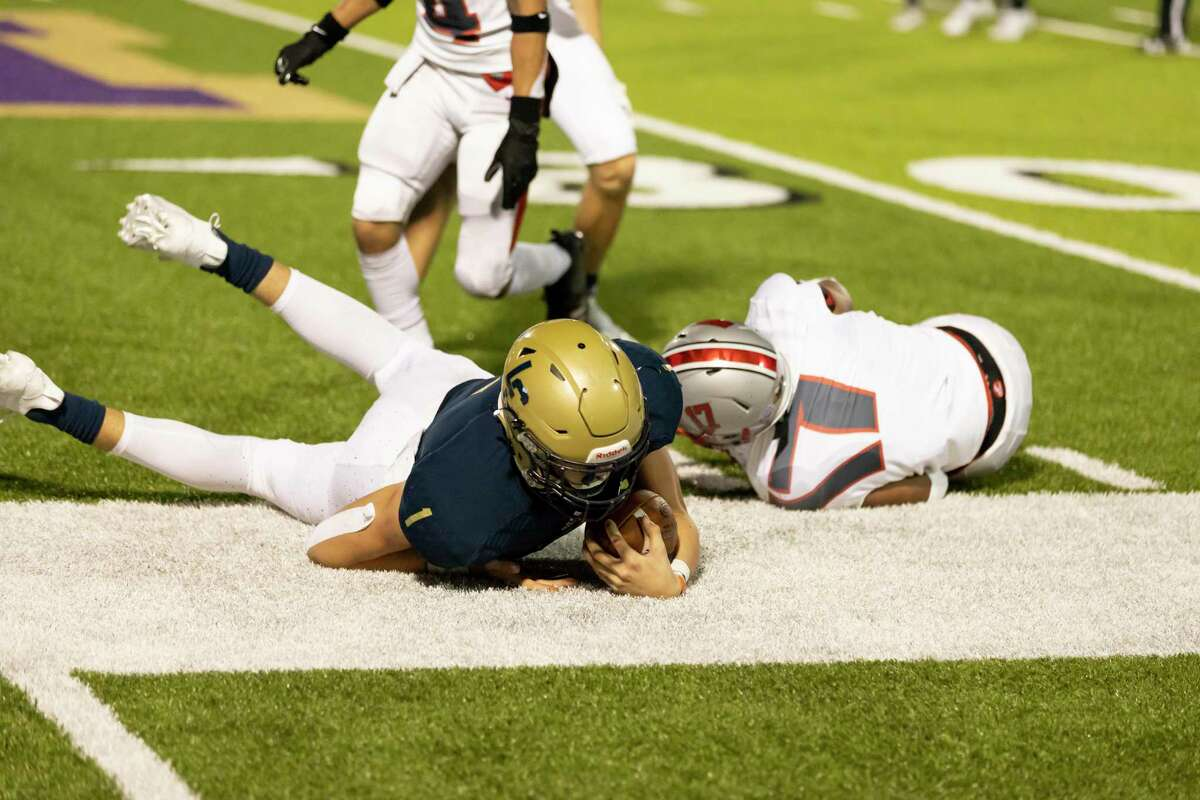 Lake Creek quarterback Ty Sexton (1) gets tackled off the sideline by Travis defensive back Dominic Nijoku (17) during the third quarter of a non-district play at MISD stadium in Montgomery, Thursday, Oct. 8, 2020.