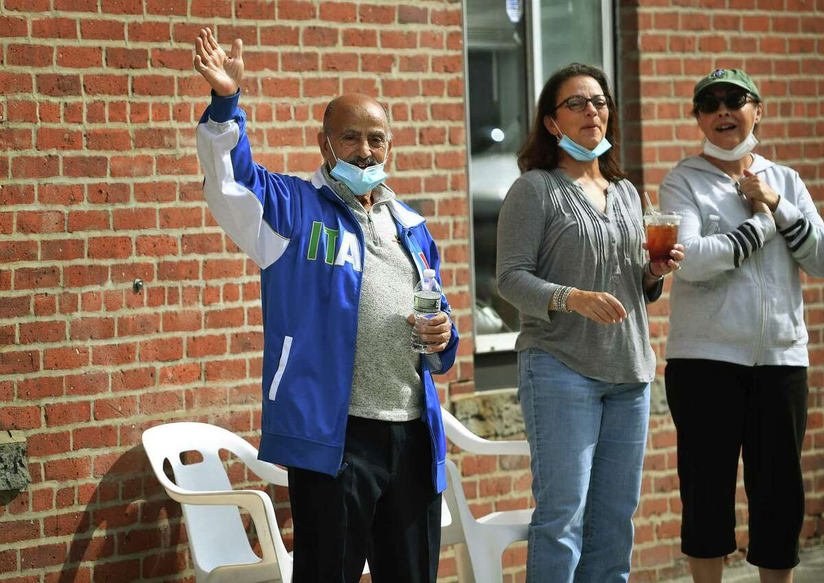 From left; Marino Battaglino, Tina Shibles, and Tina Heuring, all of Shelton, cheer on the annual Columbus Day Parade.