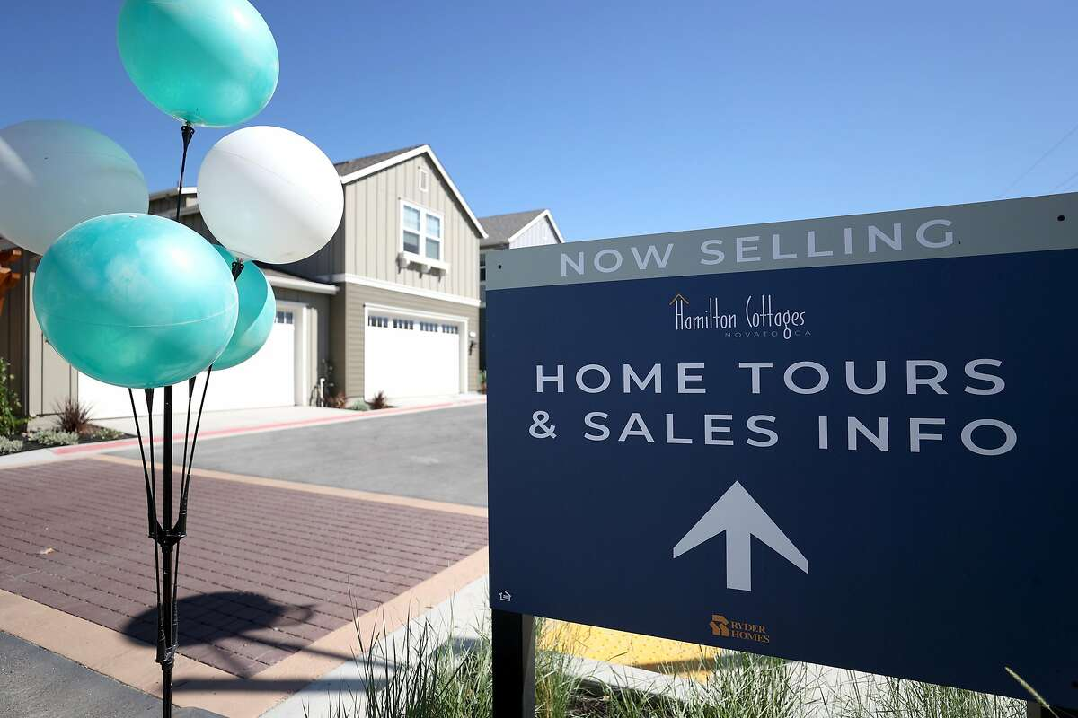 A sign points the way toward new homes for sale at Hamilton Cottages in Novato.