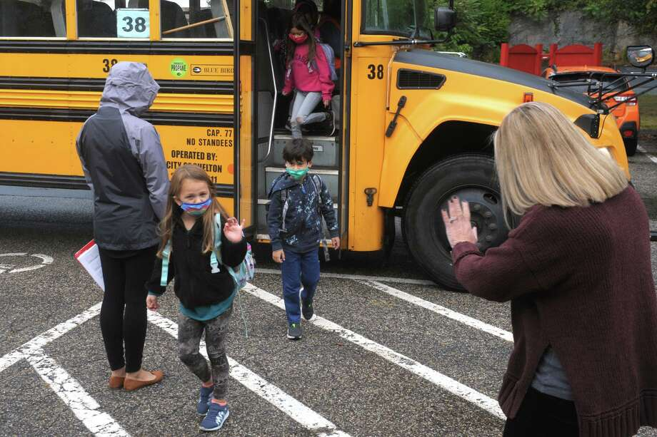 Principal Amy Yost, right, greets students as they arrive at Sunnyside Elementary School in Shelton on Tuesday. Photo: Ned Gerard / Hearst Connecticut Media / Connecticut Post