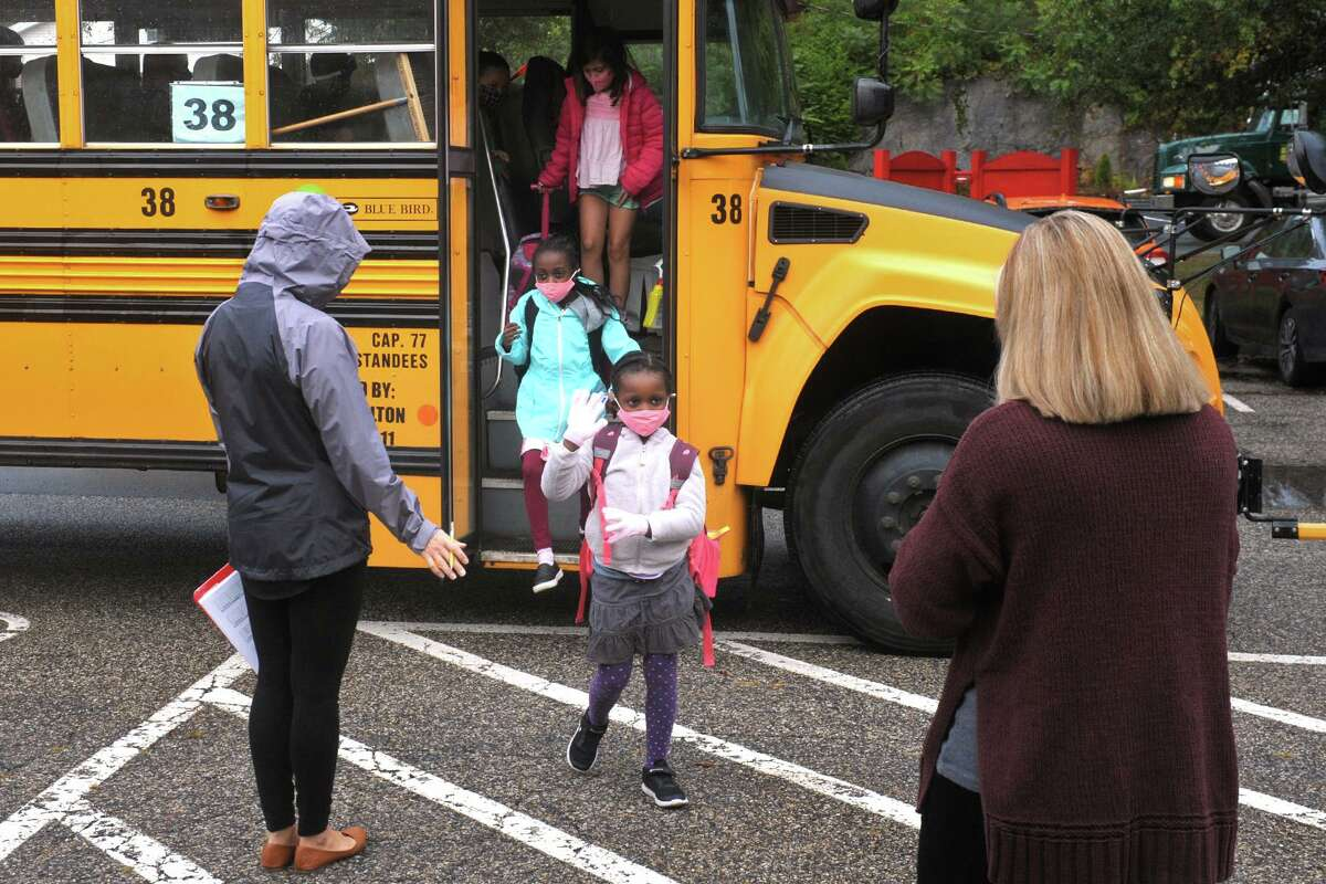 Principal Amy Yost, right, greets students as they arrive at Sunnyside Elementary School in Shelton on Tuesday.