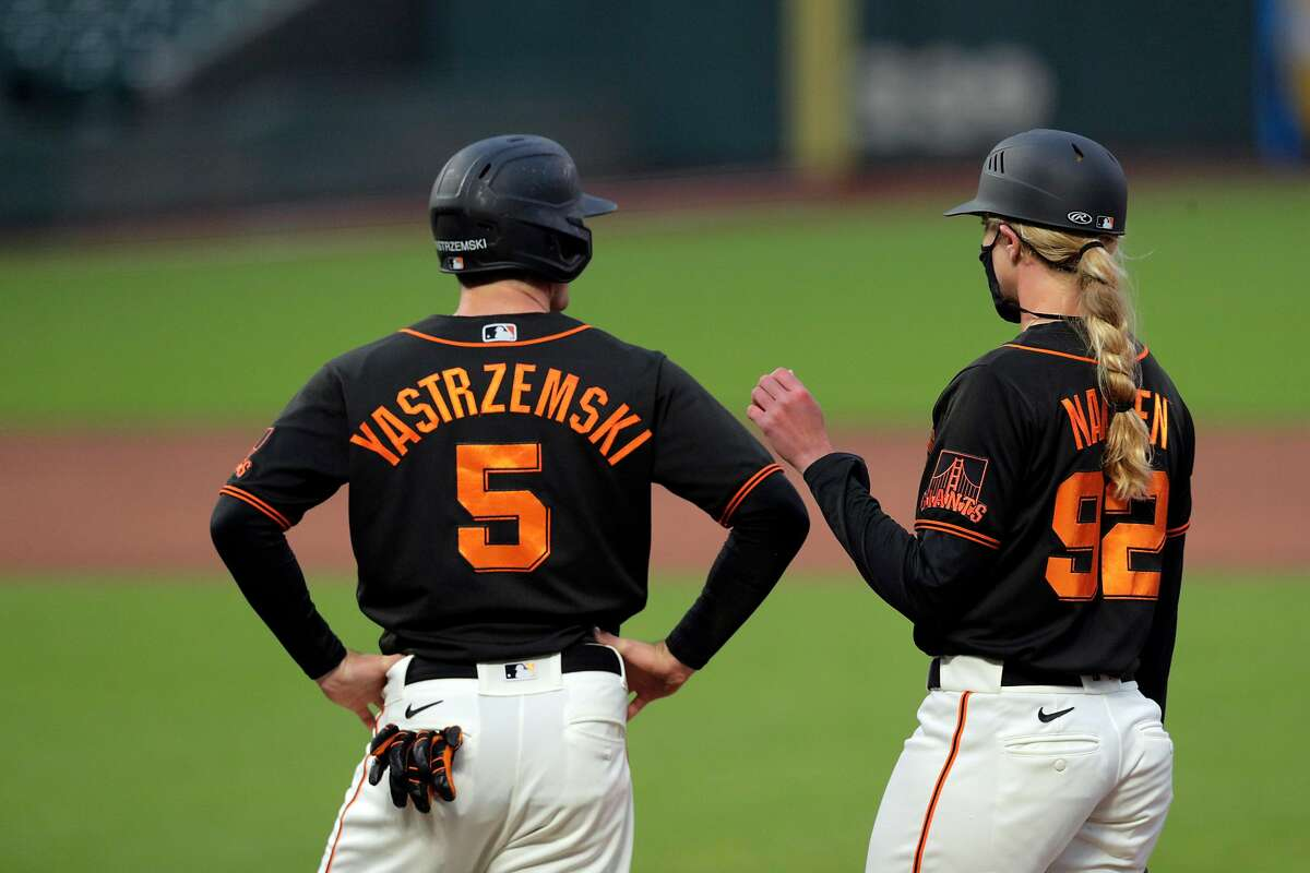 Giants first base coach Alyssa Nakken, right, chats with Mike Yastrzemski (5) in the third inning after he walked as the San Francisco Giants played the Oakland Athletics in a summer exhibition game at Oracle Park in San Francisco, Calif., on Tuesday, July 21, 2020.