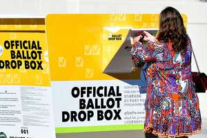 A woman casts her ballot for thr 2020 US Elections at an officla Orange County ballot drop-box at the Orange County Registrar's Office in Santa Ana, California on October 13, 2020. - The Republican Party in California has locked horns with state authorities, saying it will defy a cease-and-desist order to remove unauthorized ballot boxes it has put up in three counties across the state. (Photo by Frederic J. BROWN / AFP) (Photo by FREDERIC J. BROWN/AFP via Getty Images)