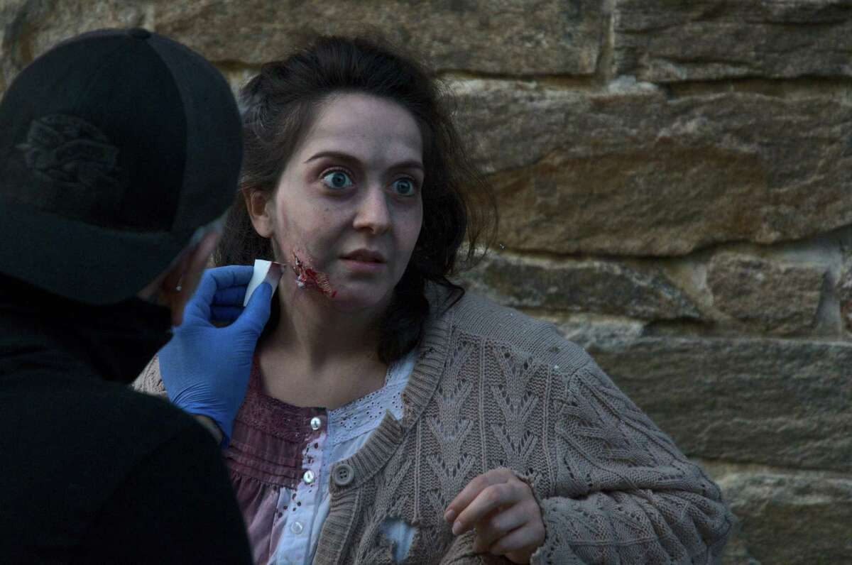 """Special FX make-up artist, Justin Talarski, applies a fake wound to actress, Samantha Holomakoff, before the filming of the Norwalk Historical Society's """"A Haunting at Mill Hill - The Movie."""" The movie will replace the historical society's regular Haunting at Mill Hill fundraiser since COVID-19 prevented safe in-person events."""