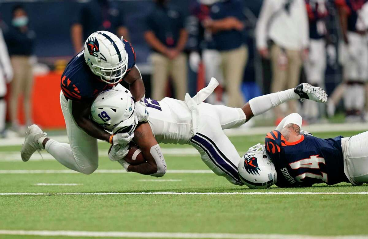 Stephen F. Austin wide receiver Xavier Gipson, center, is hit by UTSA defenders Rashad Wisdom, left, and SaVion Harris, right, after a catch during the second half of an NCAA college football game, Saturday, Sept. 19, 2020, in San Antonio. (AP Photo/Eric Gay)