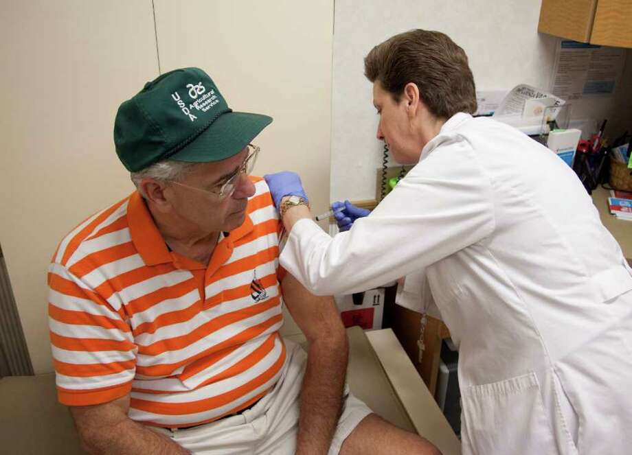Joe Garbarino of Bethesda, Md., left, gets a flu shot from nurse practitioner Susan Brown, Friday, Aug.  27, 2010, in Rockville, Md. It's flu-shot season again, and for the first time health authorities are urging nearly everyone to get vaccinated _ and people 65 or older even can choose to try a new high-dose version. (AP Photo/Evan Vucci) Photo: Evan Vucci / AP