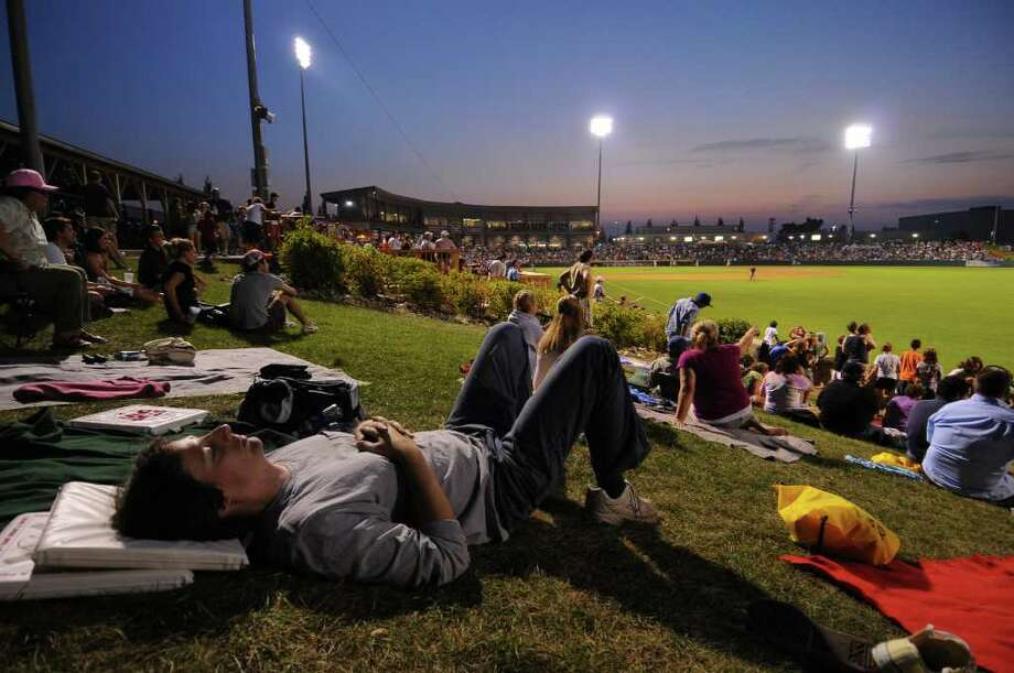 John Zieske of Altamont takes a rest in the right-field picnic area just after sunset and after a day of work, as his wife and two children wander around Joseph Bruno Stadium during a Valley Cats game on Monday. (Philip Kamrass / Times Union) Photo: Philip Kamrass