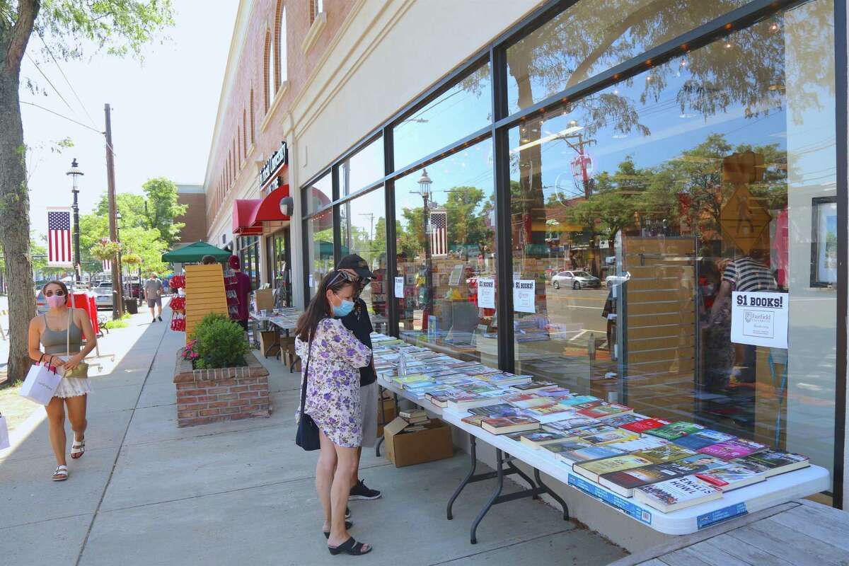 Carin Jamieson and Ed Caliri of Newtown check out the books outside of the Fairifeld University Bookstore at the annual Sidewalk Sale & Street Fair on Saturday, July 18, 2020, in Fairfield, Conn.