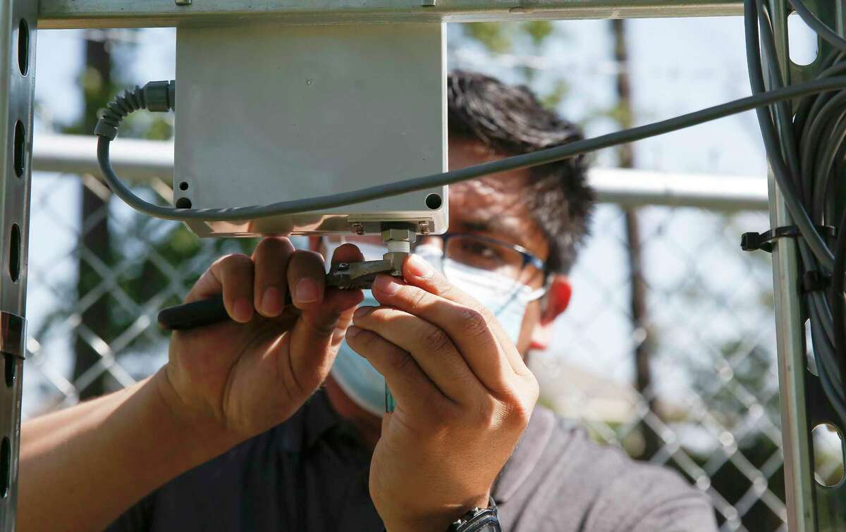 Elvis Martinez, an air monitor coordinator, works on adding a part to an air monitor behind the North Channel Library in Houston on Monday, Oct. 12, 2020.