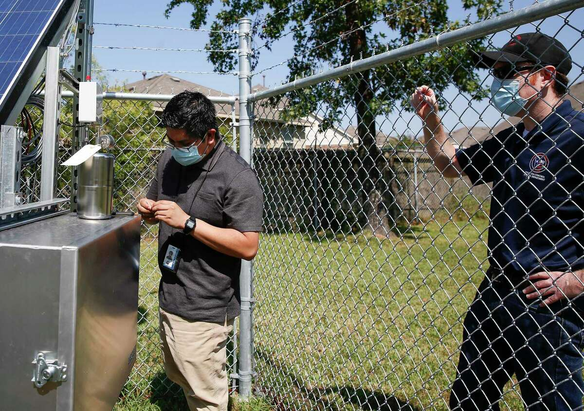 Elvis Martinez, an air monitor coordinator, works while Matt Van Vleck, air supervisor watches behind the North Channel Library in Houston on Monday, Oct. 12, 2020.