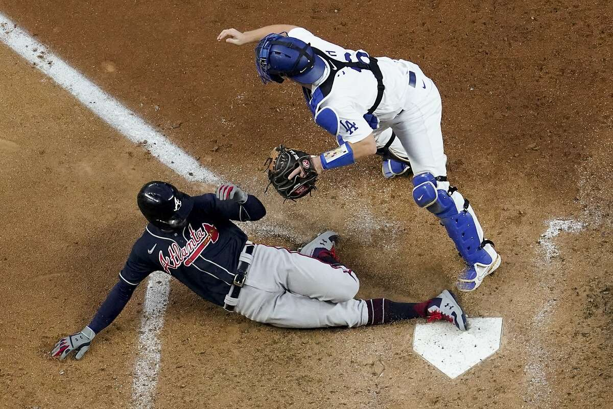 The Braves' Nick Markakis scores past Dodgers catcher Will Smith on a double by Cristian Pache during the fifth inning.