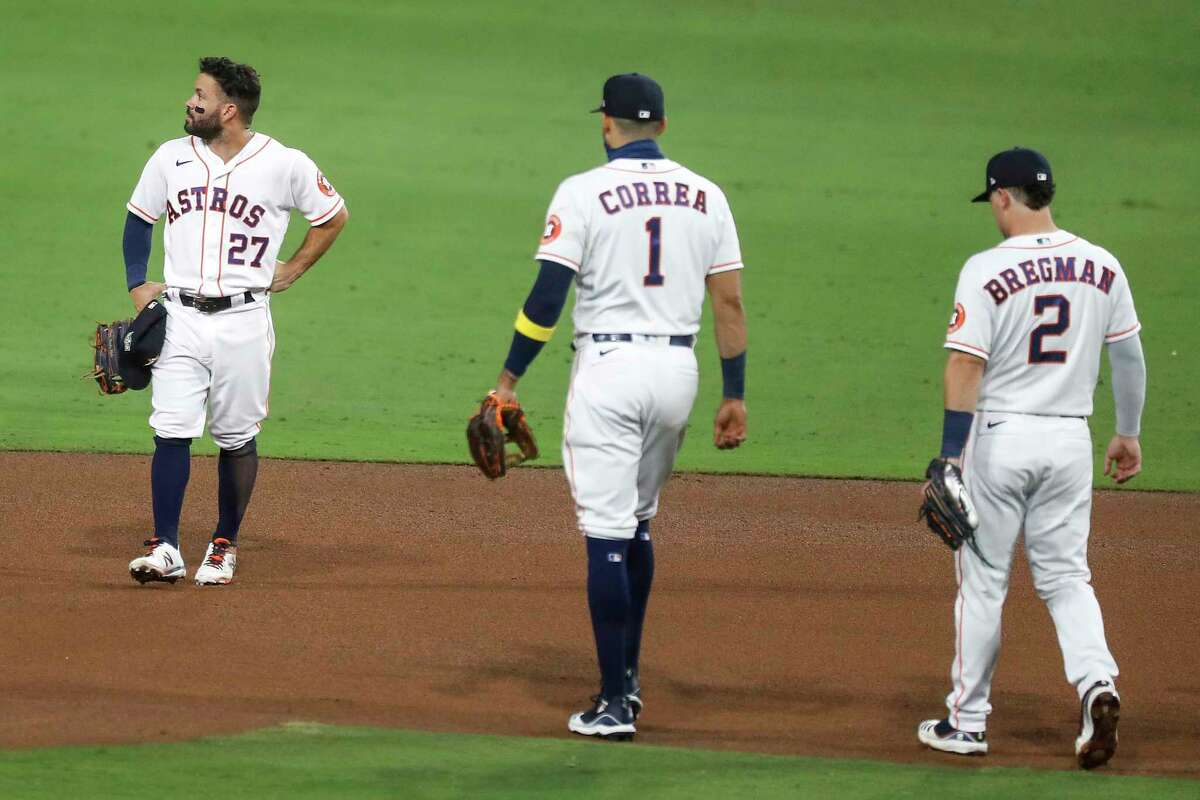 Houston Astros Jose Altuve (27) stands on the infield as teammates Carlos Correa (1) and Alex Bregman (2) walk over to him after Altuve committed an error on a grounder by Tampa Bay Rays Brandon Lowe of Game 3 of the American League Championship Series at Petco Park Tuesday, Oct. 13, 2020, in San Diego.