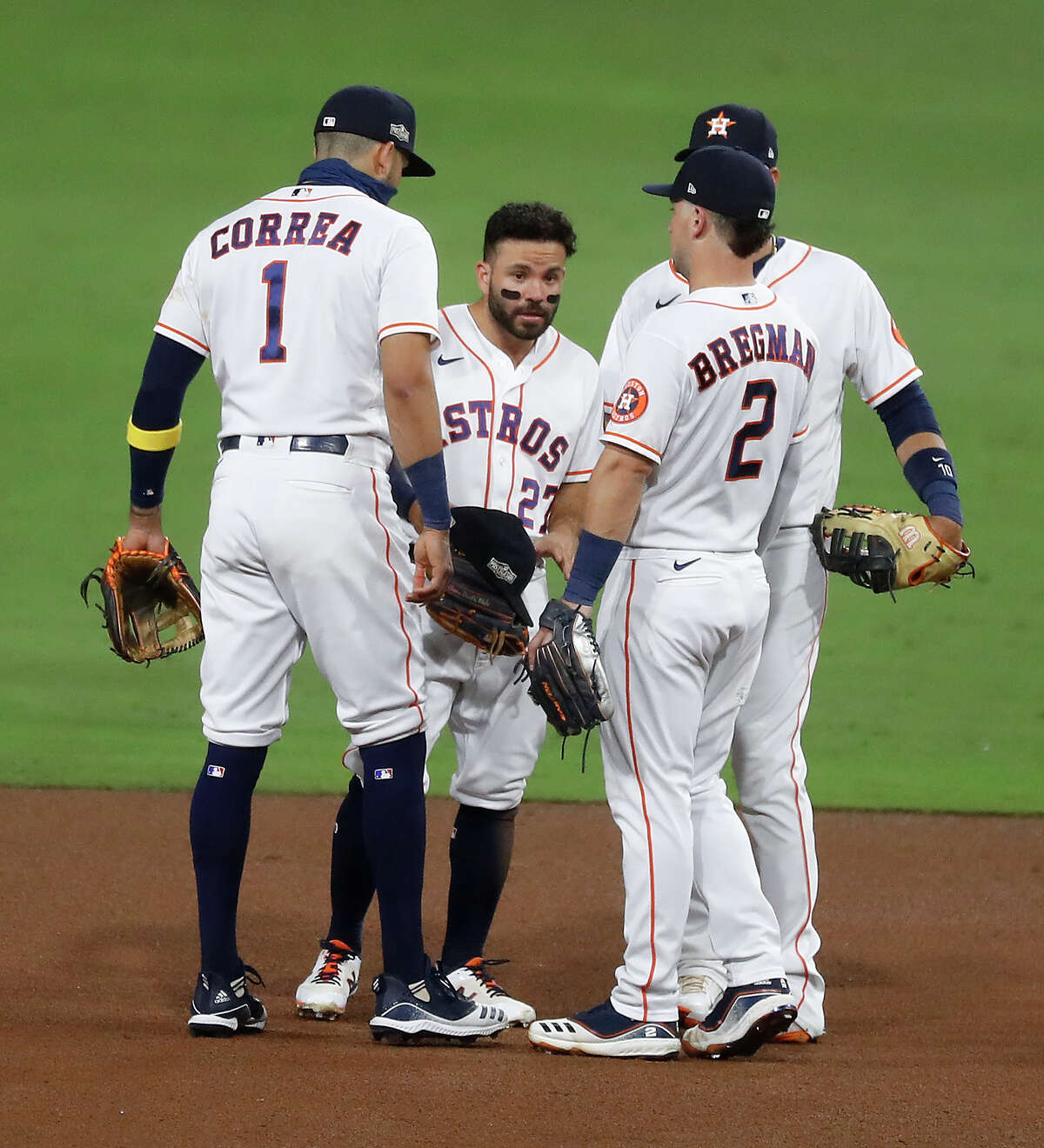 Houston Astros Jose Altuve (27) stands with teammates Carlos Correa (1) and Alex Bregman (2) and Yuli Gurriel after Altuve committed an error on a grounder by Tampa Bay Rays Brandon Lowe of Game 3 of the American League Championship Series at Petco Park Tuesday, Oct. 13, 2020, in San Diego.