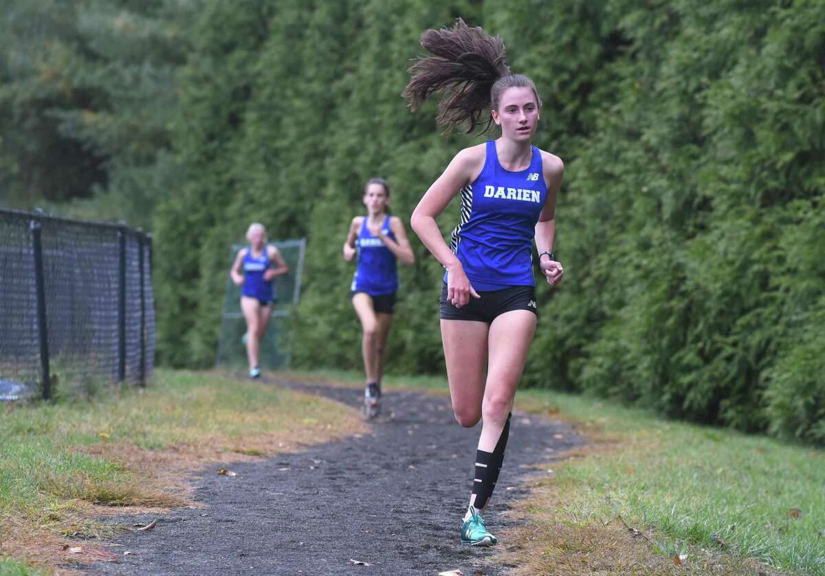 Darien's Mairead Clas leads teammates Hope Johnson and Julia Raia along the new cross country course at Darien High School during a meet against Stamford on Tuesday.