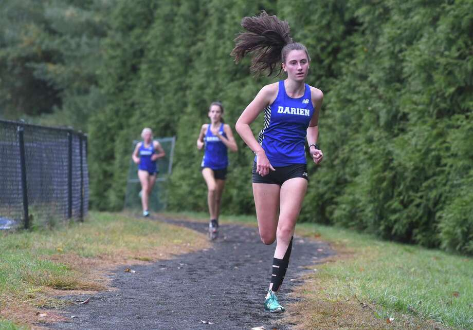 Darien's Mairead Clas leads teammates Hope Johnson and Julia Raia along the new cross country course at Darien High School during a meet against Stamford on Tuesday. Photo: David Stewart / Hearst Connecticut Media / Connecticut Post