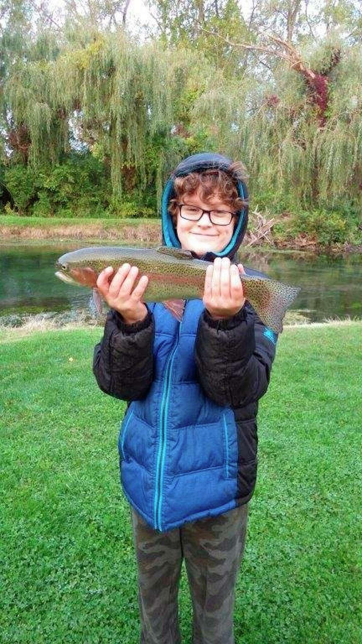 Eleven-year-old Reese Lounsbury displays a dandy rainbow trout. (Tom Lounsbury/Hearst Michigan)