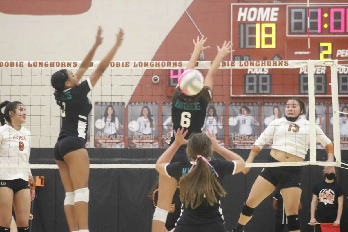 Victoria Thomas (13) attempts to put down one of her kills Tuesday night as the Memorial duo of Kindahl Smith (6) and Destini Payne bid to prevent it.