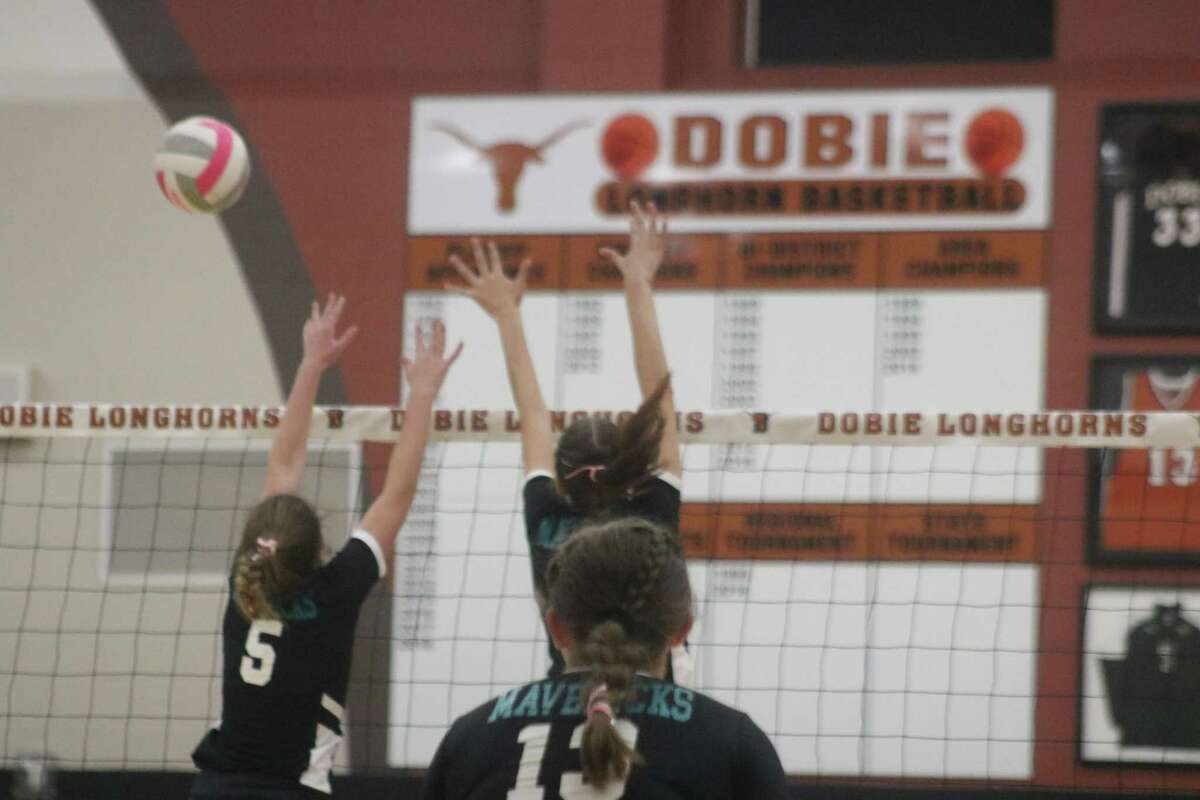 Memorial's Emma Carro and a teammate may have forced a Dobie kill attempt to sail long during Tuesday's big match in the Longhorn Gym.