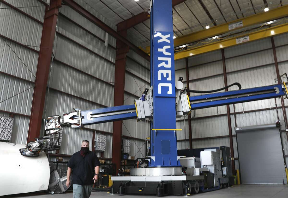 The Laser Coating Removal Robot engineered by XYREC, is a 72-foot-tall paint stripping machine that will be used to remove paint from aircraft, on Tuesday, Oct. 13, 2020. Lucky Nichols is a technician with XYREC.