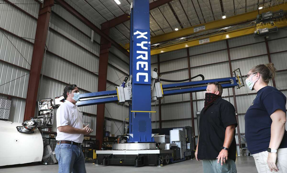 Paul Evans, left, Director of Research and Development at Southwest Researc Institute, discusses the operations of the LCRR with Lucky Nichols, center and Terri Nichols, both of XYREC. The Laser Coating Removal Robot engineered by XYREC, is a 72-foot-tall paint stripping machine that will be used to remove paint from aircraft, on Tuesday, Oct. 13, 2020.