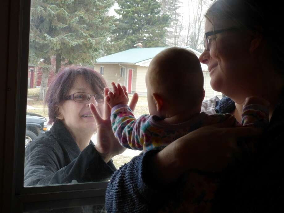 Maya Grace Fraley reaches for her grandmother during the pandemic lockdown. Photo: Scott Fraley/News Advocate