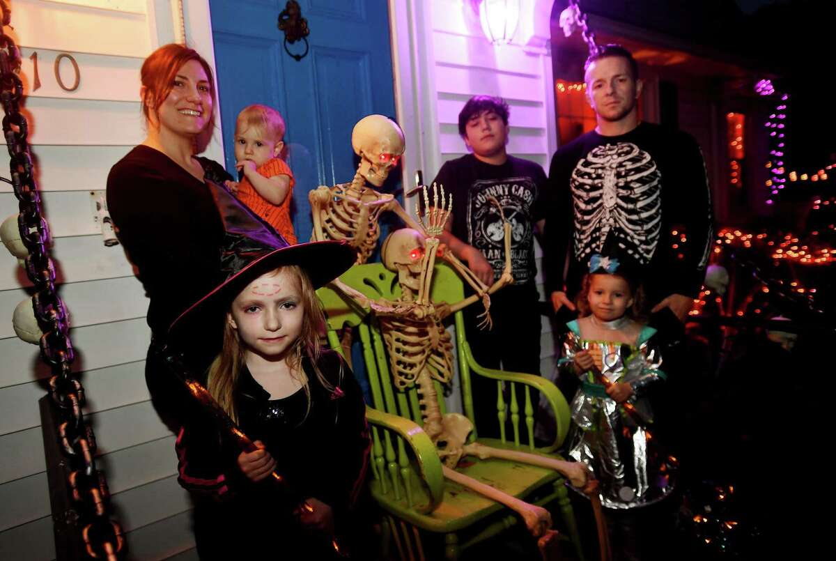 """From left; Rebecca Lore, Aerokai Sloate, 15 months, Ember Sloate, 5, Dustin Sloate, 12, Icelynn Sloate, 3, and Sean Sloate, outside their Ridgeview Avenue home, part of the Trumbull Terror Trail, in Trumbull , Conn. on Tuesday, October 13, 2020. Lore, a theater lighting designer, said she has always enjoyed Halloween decorating. But like Smith-Solomon, the COVID-19 pandemic has all but reduced her work responsibilities, and as a result, has made her house even more of a neighborhood attraction. """"We've always decorated, and each year you add something and build on what you did last year,"""" she said. """"But this year we've done the most we've ever done. We really went all out and this year it's extra important for people to have something for families to do."""""""