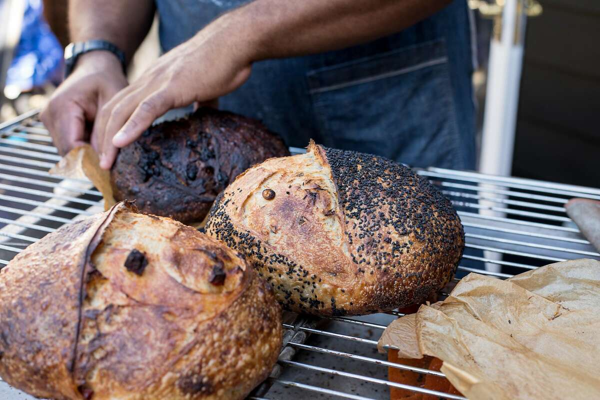 Rize Up Sourdough boules come in a variety of flavors, such as Hogs in Heaven (front), scallion sesame, and chocolate.