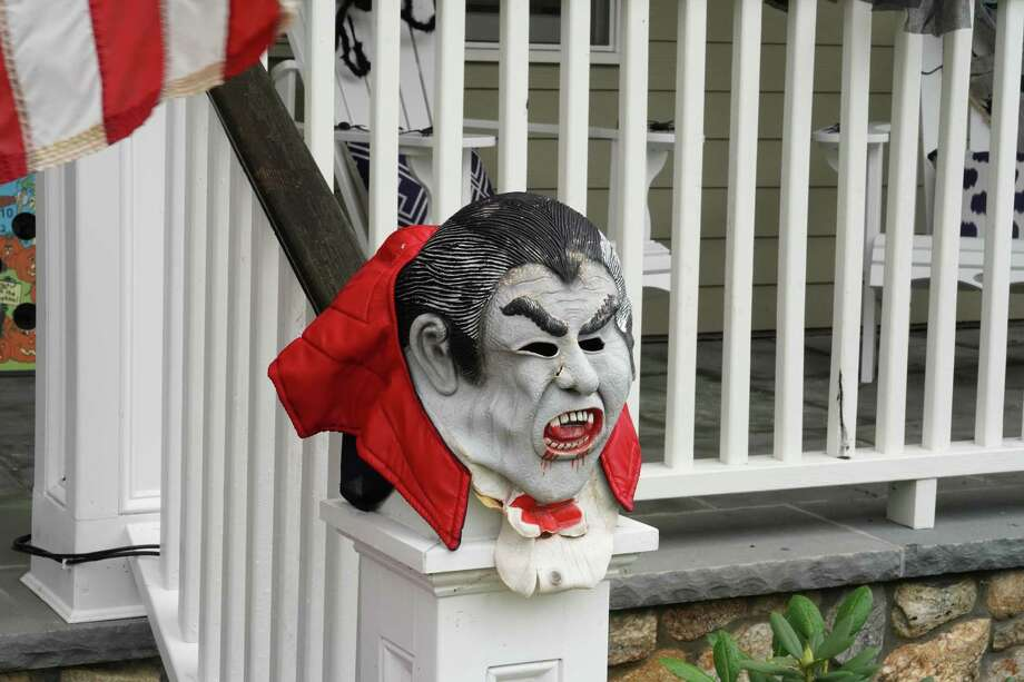 Traditional Halloween masks may be better used as decorations instead of on the face this year, since they can be dangerous if coupled with the face covering used to prevent the spread of COVID-19. The mask on the stair railing is just one of the ways the Dimuzio family's home on Summer Street is decked out for Halloween. Photo: Grace Duffield / Hearst Connecticut Media