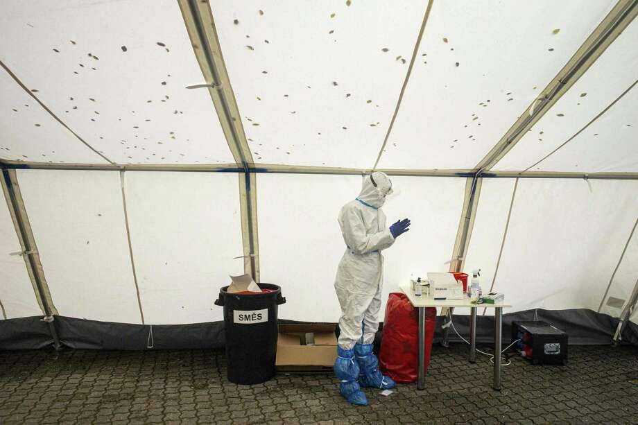 A medical worker wearing personal protective equipment waits for a patient at the drive-in Covid-19 coronavirus testing station on October 14, 2020 in Prague. (Photo by Michal Cizek / AFP) (Photo by MICHAL CIZEK/AFP via Getty Images) Photo: MICHAL CIZEK / AFP Via Getty Images / AFP or licensors