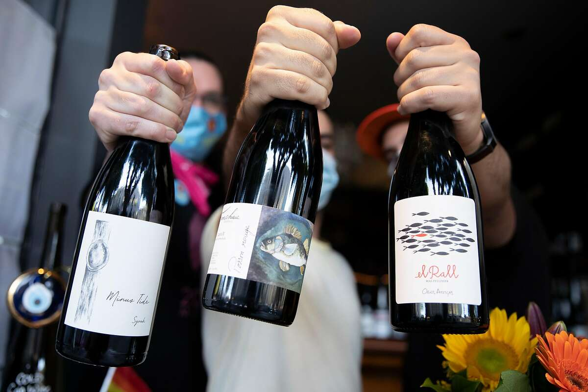 Andrew Paul Nelson, Bahman Safari and Essam Kardosh brandish bottles of wine at their pop-up wine bar, Habibi.