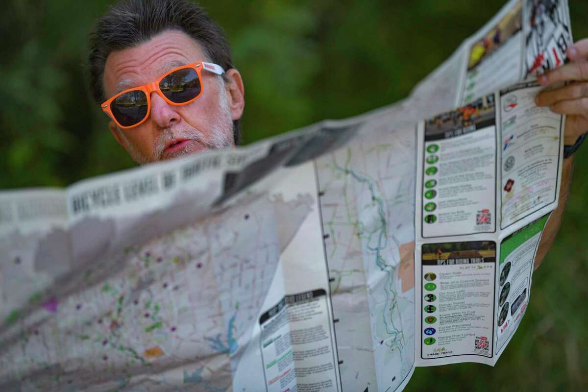 Dave Ludwig looks over a map the he uses to navigate the Salado Creek Greenway near the J Street Trailhead on Tuesday. He has walked the city's trails every day since June 1.