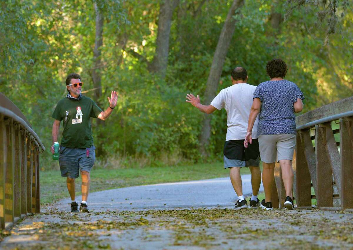 Dave Ludwig greets fellow walkers along the Salado Creek Greenway near the J Street Trailhead on Tuesday. He has walked the city's trails every day since June 1.