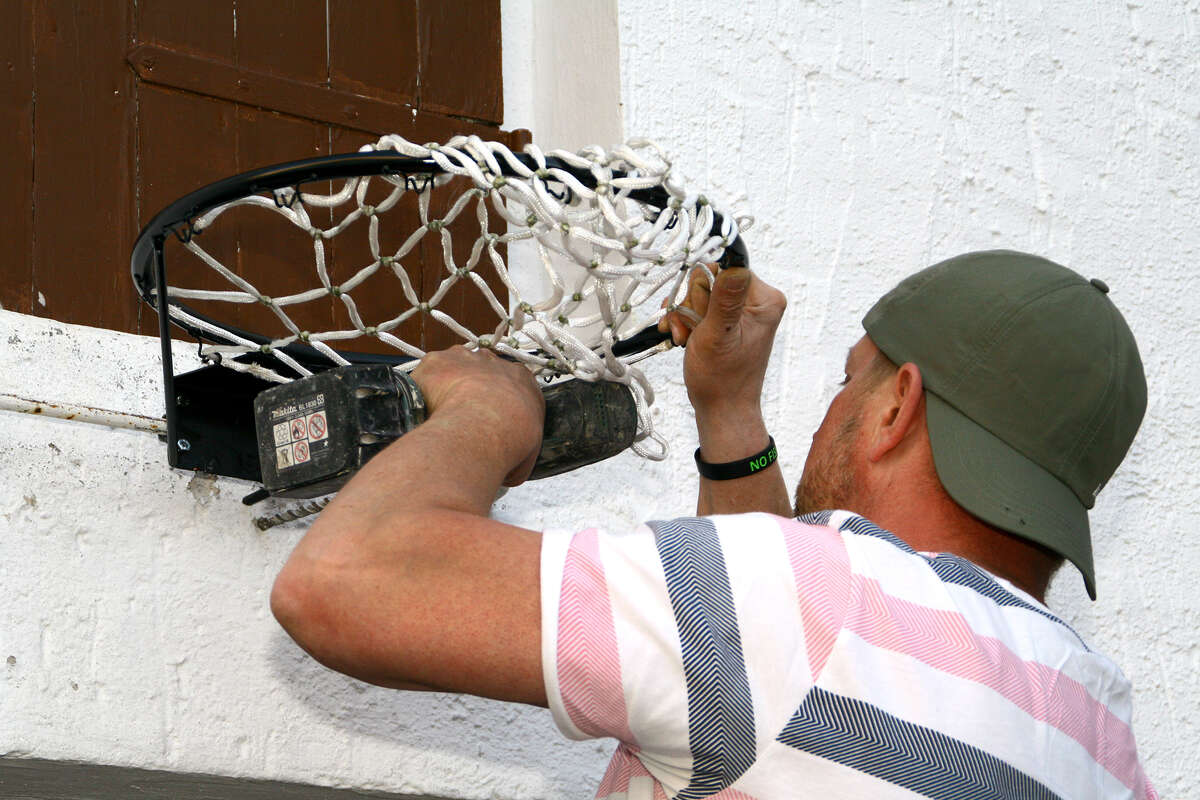A man repairs a basketball hoop.